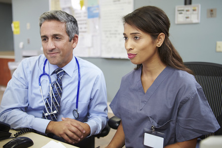 nurses station: Doctor With Nurse Working At Nurses Station Stock Photo