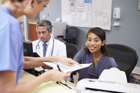 nurse and patient: Medical Staff Meeting At Nurses Station Stock Photo