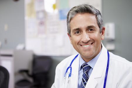 hispanic: Portrait Of Doctor Working At Nurses Station