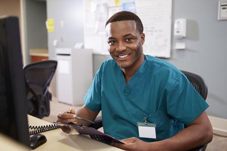 Portrait Of Male Nurse Working At Nurses Station