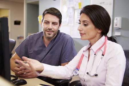 Female Doctor With Male Nurse Working At Nurses Station photo