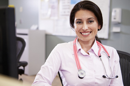 Portrait Of Doctor Working At Nurses Station photo