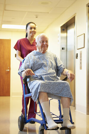 Senior Male Patient Being Pushed In Wheelchair By Nurse photo