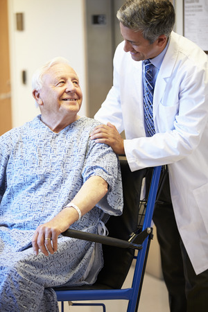 Senior Male Patient Being Pushed In Wheelchair By Doctor