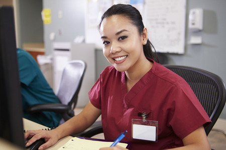 Portrait Of Female Nurse Working At Nurses Station photo