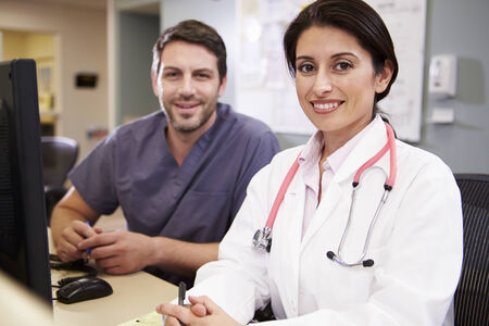 nurses station: Female Doctor With Male Nurse Working At Nurses Station Stock Photo