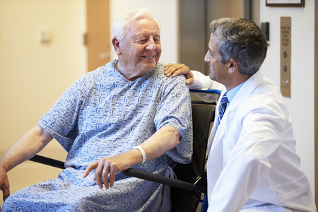 Hogere Mannelijke Patiënt die wordt geduwd in Rolstoel Door Doctor Stockfoto