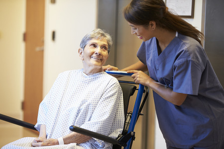 Senior Female Patient Being Pushed In Wheelchair By Nurse photo