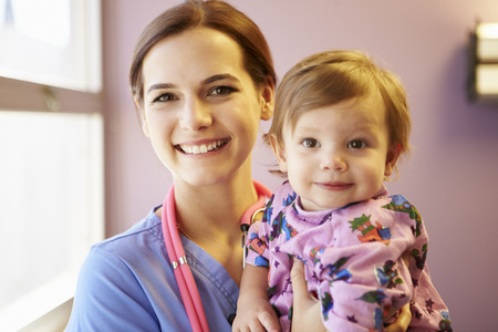 hospital gown: Young Girl Being Held By Female Pediatric Nurse Stock Photo