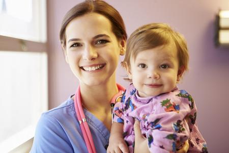 pediatric nurse: Young Girl Being Held By Female Pediatric Nurse Stock Photo