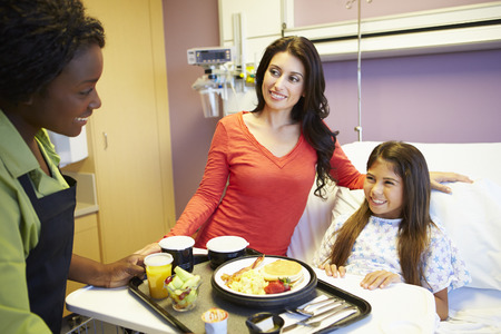 Young Girl Being Served Lunch In Hospital Bed