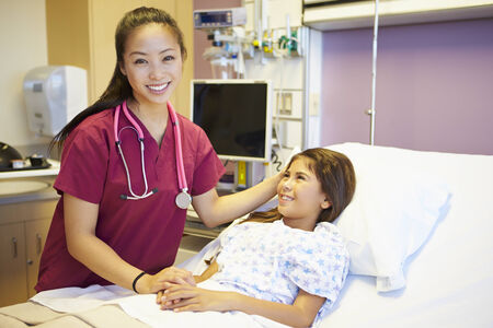 Young Girl Talking To Female Nurse In Hospital Room photo