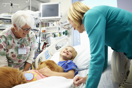 Young Girl Being Visited In Hospital By Therapy Dog photo