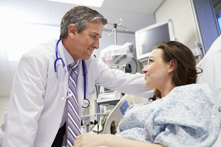 hospitales: Paciente de sexo femenino que habla con el doctor de sexo masculino en la sala de emergencias Foto de archivo