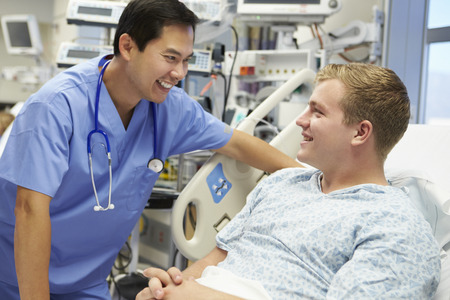 Young Male Patient Talking To Male Nurse In Emergency Room photo