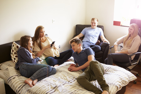 boy 16 year old: Group Of Teenagers Relaxing In Bedroom