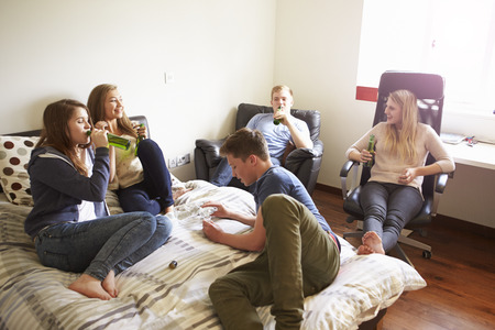 tomando alcohol: Grupo de adolescentes que beben alcohol en el dormitorio