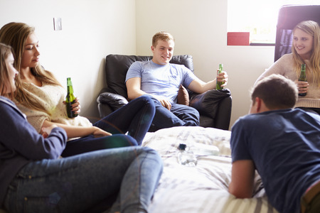 Group Of Teenagers Drinking Alcohol In Bedroom photo