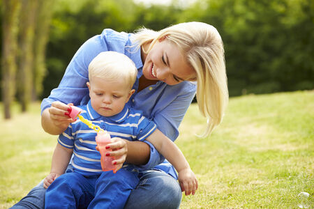 Mother Blowing Bubbles For Young Boy In Garden photo