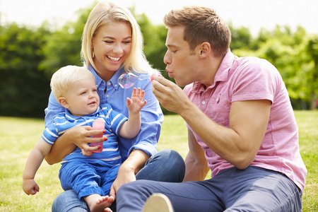 Parents Blowing Bubbles For Young Boy In Garden photo