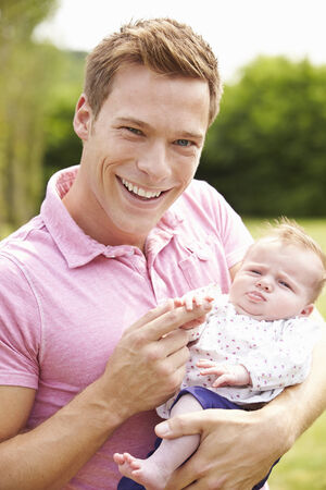 Proud Father Holding Baby Daughter In Garden photo