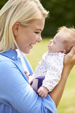 Loving Mother Holding Baby Daughter In Garden photo