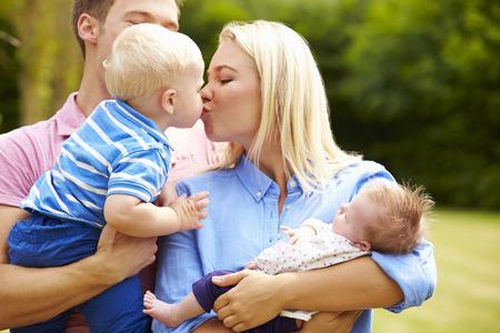 Parents Holding Young Children In Garden photo