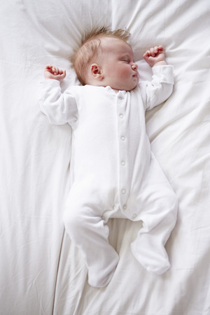 gro: Newborn Baby Girl Sleeping In Bed Stock Photo