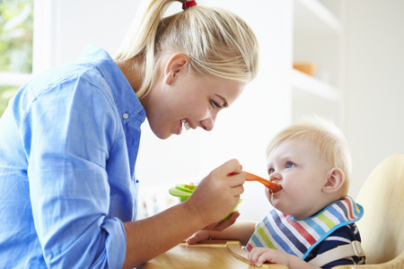 baby eating: Mother Feeding Baby Boy In High Chair