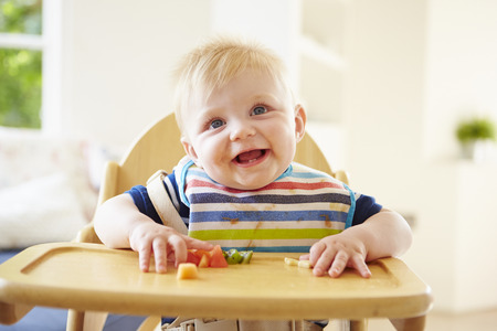 Baby Boy Eating Fruit In High Chair Stockfoto