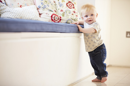 onto: Young Boy Learning To Walk By Holding Onto Furniture