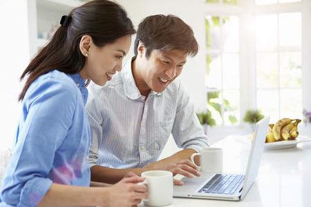Азиатский пара, глядя на ноутбук в кухне