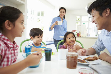 breakfast cereal: Asian Family Having Breakfast Together In Kitchen