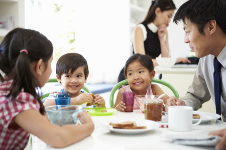 Asian Family Having Breakfast Before Husband Goes To Work