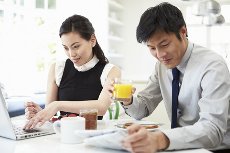 Asian Couple With Laptop And Newspaper At Breakfast photo