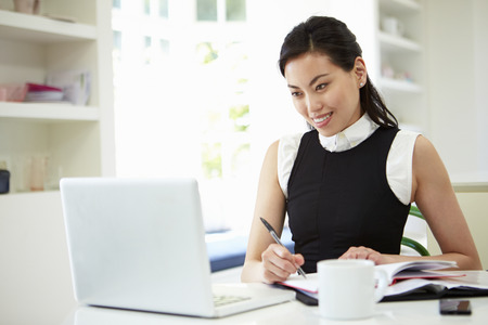 working from home: Asian Businesswoman Working From Home On Laptop Stock Photo