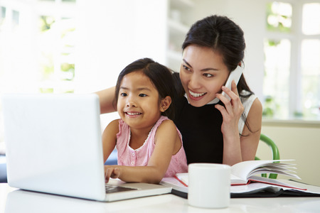 asian ladies: Busy Mother Working From Home With Daughter