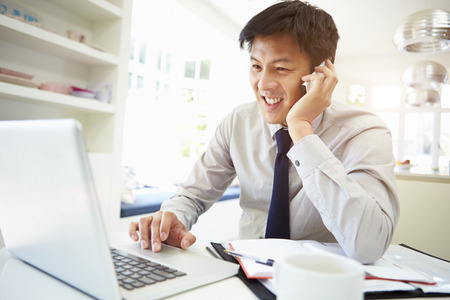 Asian Businessman Working From Home Using Mobile Phone photo