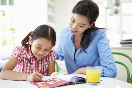 Mother Helping Daughter With Homework photo