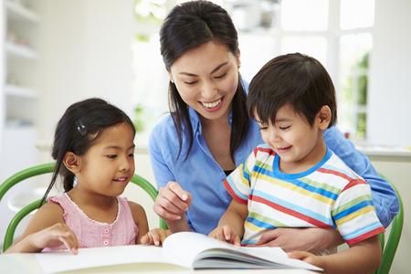 deberes: Madre ayudar a los ni�os con la tarea Foto de archivo