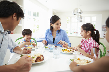 familia de cinco: Familia asi�tica sentado en la mesa Comer comida junto Foto de archivo