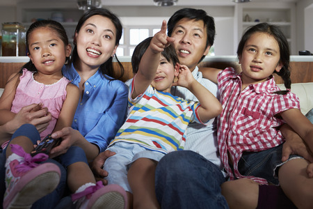 Asian Family Sitting On Sofa Watching TV Together photo