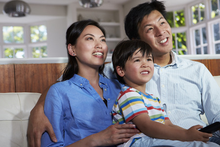 woman watching tv: Asian Family Sitting On Sofa Watching TV Together Stock Photo
