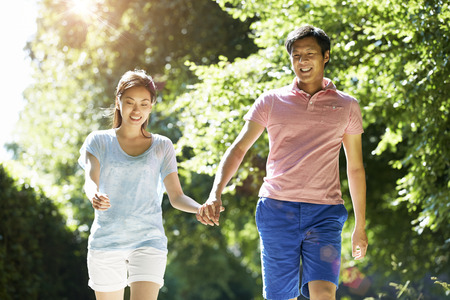 田園地帯での散歩でロマンチックなアジア カップル 写真素材