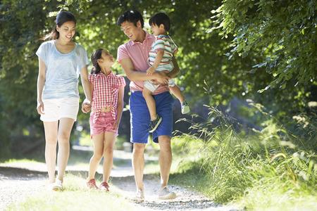 niños caminando: Familia asiática disfruta de la caminata en Campo