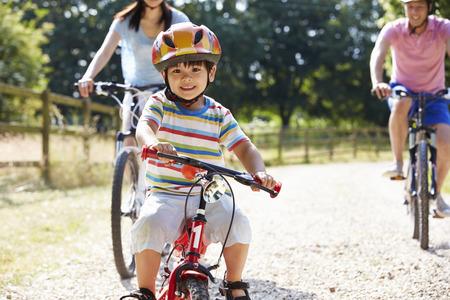 andando en bicicleta: Familia asiática en paseo del ciclo En Campo