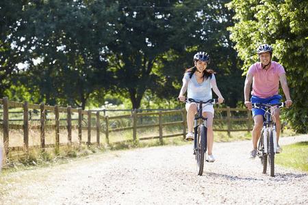 andando en bicicleta: Pareja asiática en paseo del ciclo En Campo