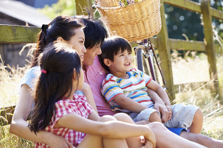 Asian Family Resting By Fence With Old Fashioned Cycle Stock Photo