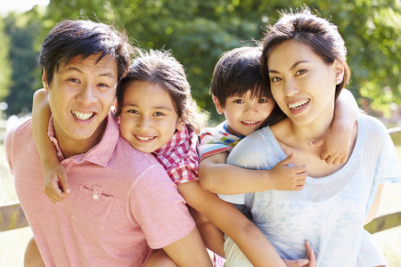 Portrait Of Asian Family Enjoying Walk In Summer Countryside