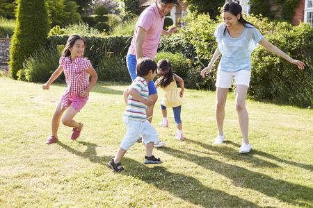 niñas jugando: Familia asiática que juega en jardín del verano junto